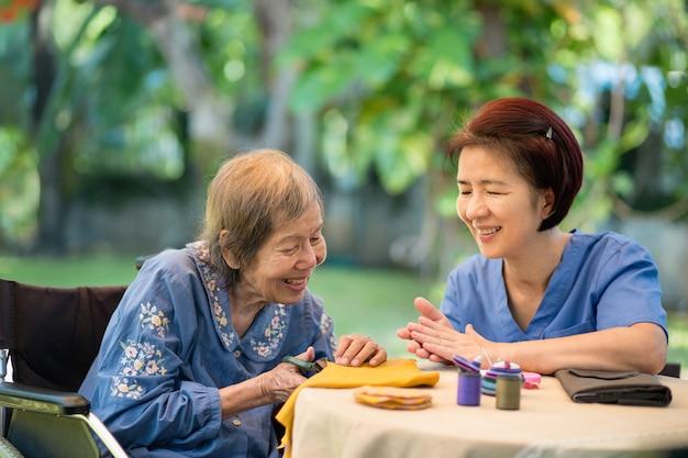 Mulher idosa com cuidador na terapia ocupacional de artesanato de agulha