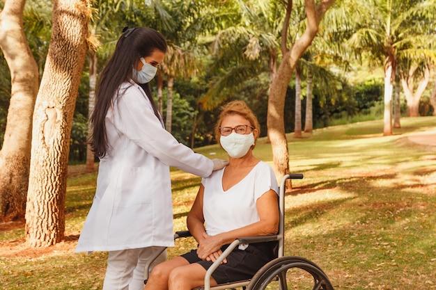Mulher idosa com deficiência com cuidador no jardim da casa de repouso