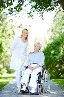 Mulher idosa com deficiência e cuidador