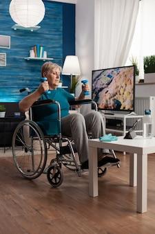 Mulher idosa com deficiência em cadeira de rodas alongando músculos dos braços e exercitando resistência corporal