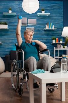 Mulher idosa com deficiência em cadeira de rodas levantando o braço, treinando a resistência dos músculos com halteres