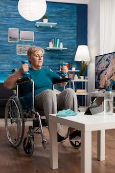 Mulher idosa com deficiência segurando halteres de treinador, fazendo exercícios com os braços