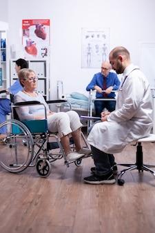 Mulher idosa com deficiência sentada em cadeira de rodas durante consulta médica na clínica de recuperação