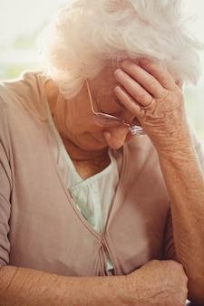 Mulher idosa com dor de cabeça em casa