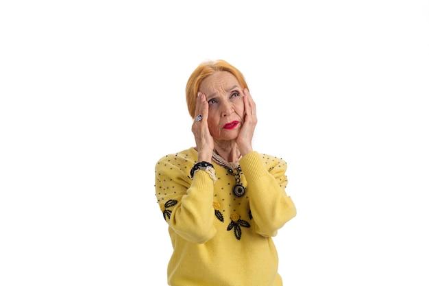 Mulher idosa com dor de cabeça isolada, mulher preocupada observando aumento da pressão intracraniana