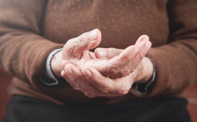 Mulher idosa com dor na mão.