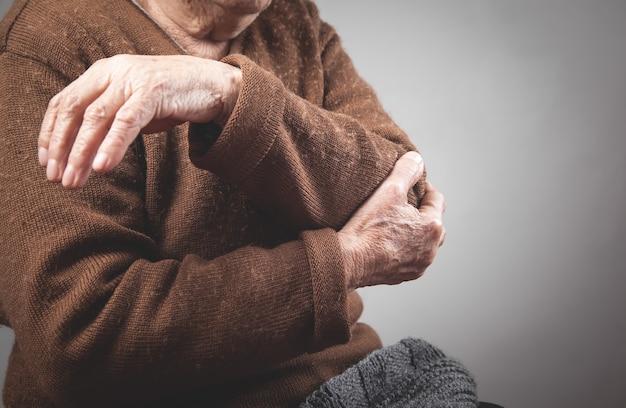 Mulher idosa com dor no cotovelo.