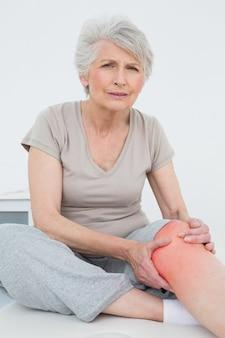 Mulher idosa com dor no joelho sentada na mesa de exame