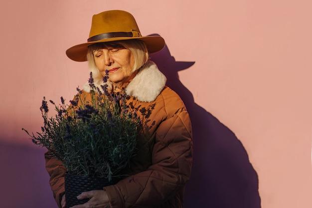 Mulher idosa com flores na sombra. mulher idosa em agasalhos carregando um vaso de flores aromáticas