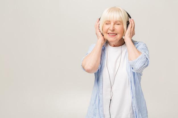 Mulher idosa com fones de ouvido ouvindo música em um telefone isolado no fundo branco
