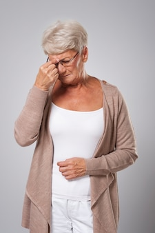 Mulher idosa com forte dor de cabeça