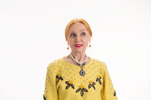 Mulher idosa com fundo branco, senhora pensativa, desviando os pensamentos e planos