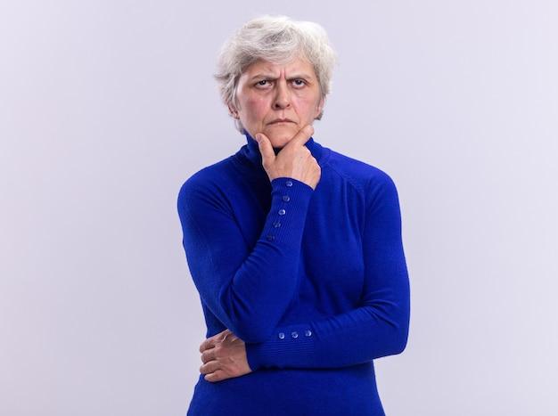 Mulher idosa com gola olímpica azul olhando para a câmera com expressão pensativa e mão no queixo em pé sobre o branco