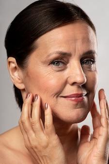 Mulher idosa com maquiagem, posando com as mãos no rosto