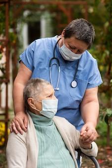 Mulher idosa com máscara médica e enfermeira