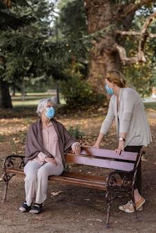 Mulher idosa com máscara médica e mulher em casa de repouso