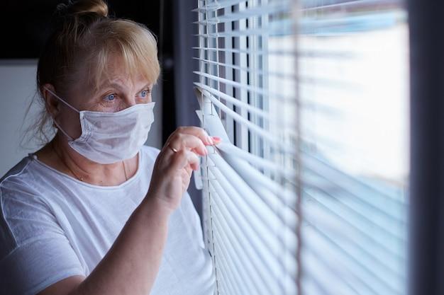 Mulher idosa com máscara médica em quarentena e auto-isolamento