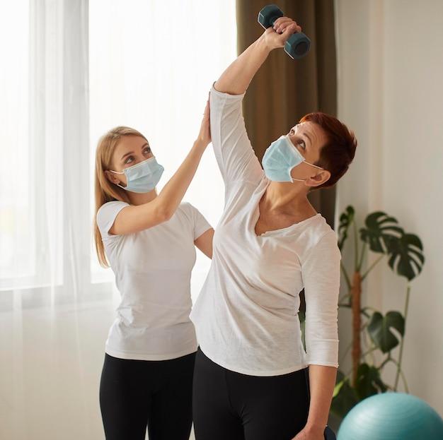 Mulher idosa com máscara médica em recuperação cobiçosa fazendo exercícios com halteres