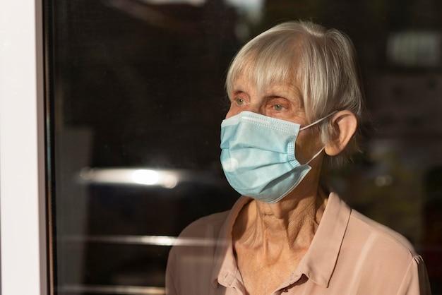 Mulher idosa com máscara médica olhando pela janela