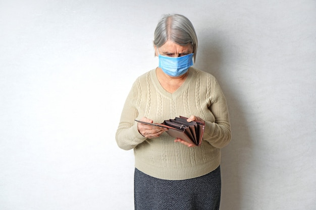 Mulher idosa com máscara médica, segurando uma carteira vazia.