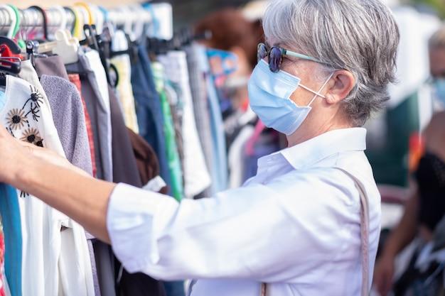Mulher idosa com máscara protetora no mercado de pulgas escolhendo roupas