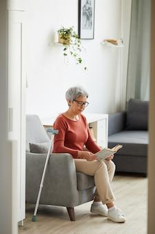 Mulher idosa com óculos, descansando no sofá e lendo um livro em casa
