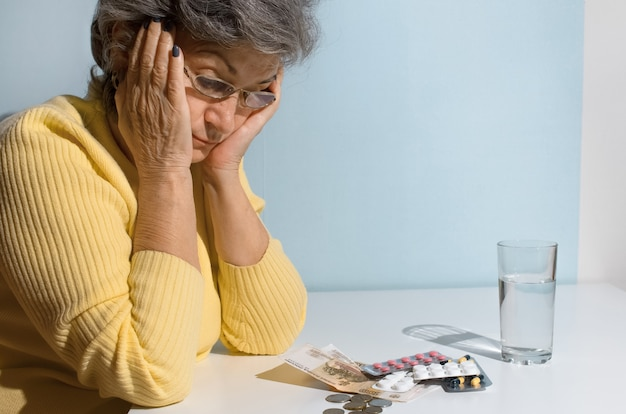 Mulher idosa com óculos, olhando para dinheiro e comprimidos em cima da mesa. conceito de depressão, preço do medicamento, custo do tratamento
