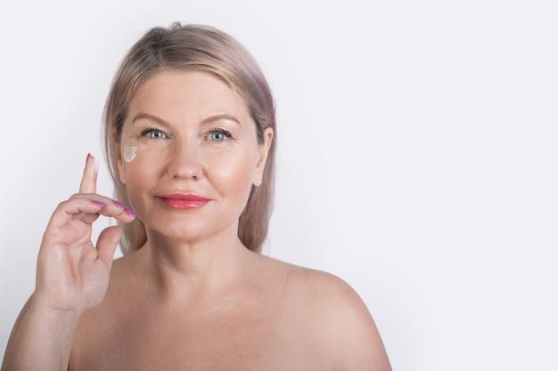 Mulher idosa com ombros nus posando em uma parede branca de estúdio anunciando algo enquanto aplica creme facial perto dos olhos