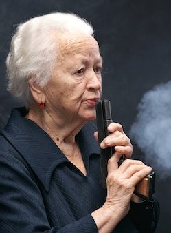 Mulher idosa com pistola em um fundo cinza