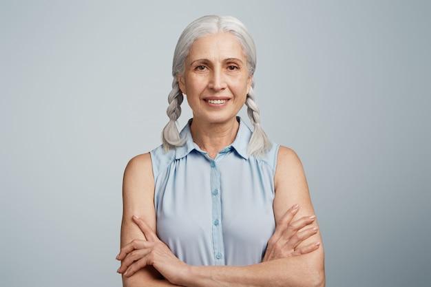 Mulher idosa com rabo de cavalo vestida com blusa azul