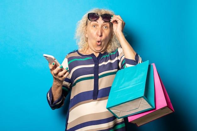 Mulher idosa com rosto surpreso usando óculos segurando sacolas de compras e telefone na superfície azul