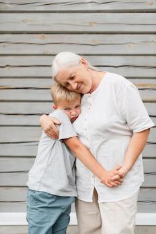 Mulher idosa com tiro médio abraçando criança