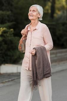 Mulher idosa com tiro médio caminhando no parque