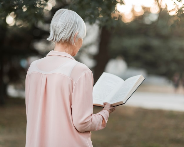 Mulher idosa com tiro médio lendo