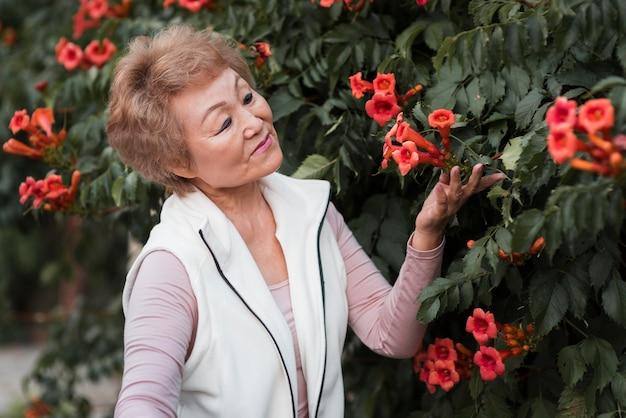 Mulher idosa com tiro médio posando com flores