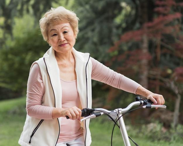 Mulher idosa com tiro médio segurando bicicleta