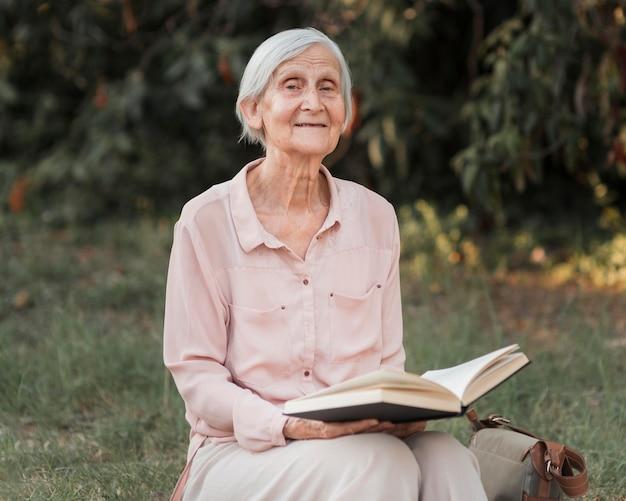 Mulher idosa com tiro médio segurando livro