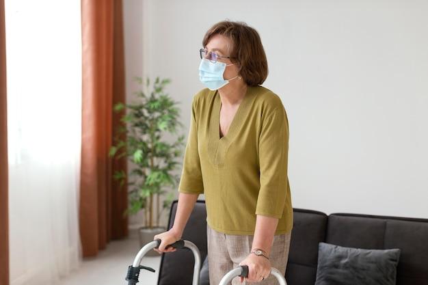Mulher idosa com tiro médio usando máscara