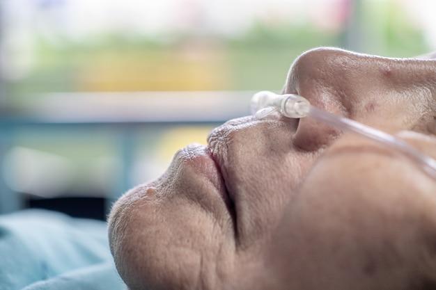 Mulher idosa com tubo de respiração nasal para ajudar na respiração