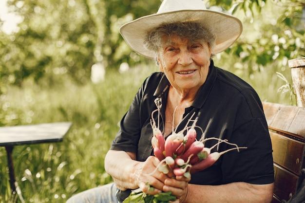 Mulher idosa com um chapéu segurando rabanetes frescos