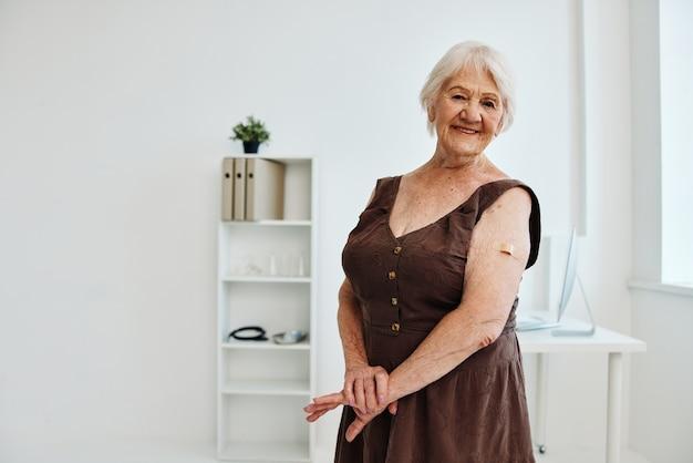 Mulher idosa com um curativo no braço passaporte de vacina covid