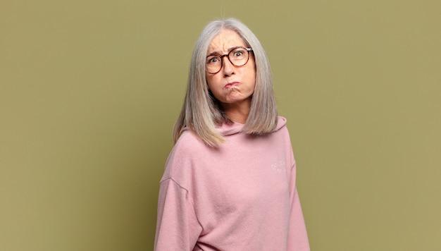 Mulher idosa com uma expressão boba, louca e surpresa, bochechas estufadas, sentindo-se recheada, gorda e cheia de comida