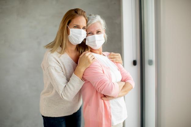 Mulher idosa com uma filha carinhosa em casa usando máscaras médicas como proteção contra o coronavírus