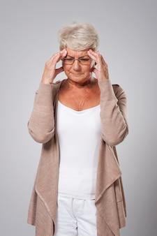 Mulher idosa com uma grande dor de cabeça