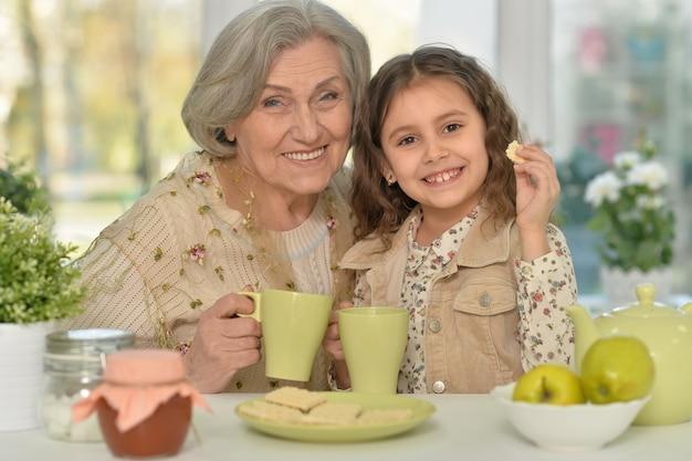 Mulher idosa com uma jovem tomando chá