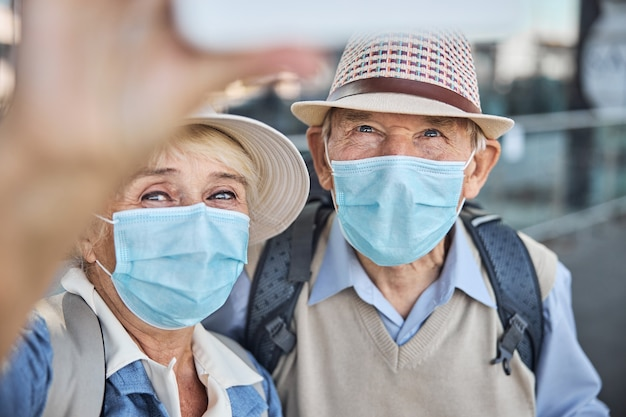 Mulher idosa com uma máscara facial fotografando a si mesma e ao cônjuge com o telefone celular
