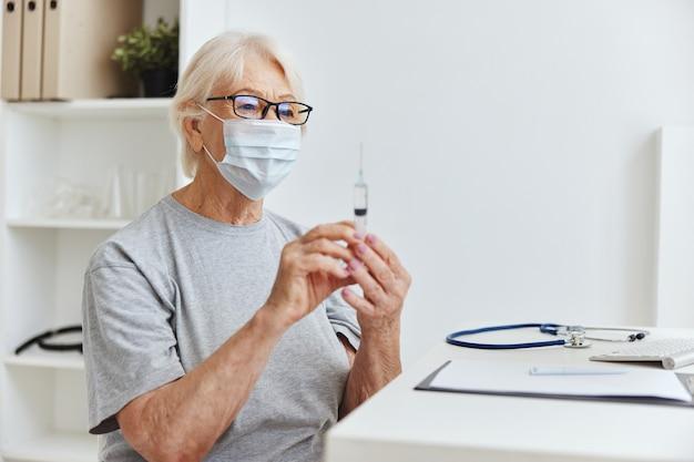 Mulher idosa com uma máscara médica segurando uma seringa em um hospital de tratamento de mãos