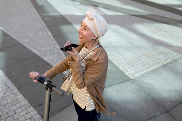 Mulher idosa com uma scooter elétrica falando ao telefone na cidade