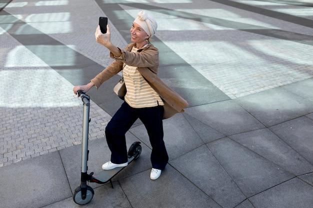 Mulher idosa com uma scooter elétrica na cidade tirando uma selfie