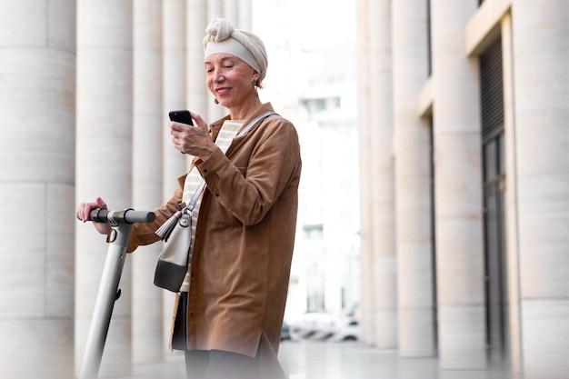 Mulher idosa com uma scooter elétrica na cidade usando smartphone